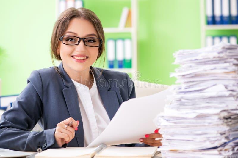 El empleado de sexo femenino joven muy ocupado con papeleo en curso fotos de archivo