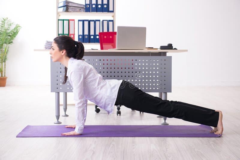 El empleado de sexo femenino joven que hace ejercicios en la oficina fotografía de archivo