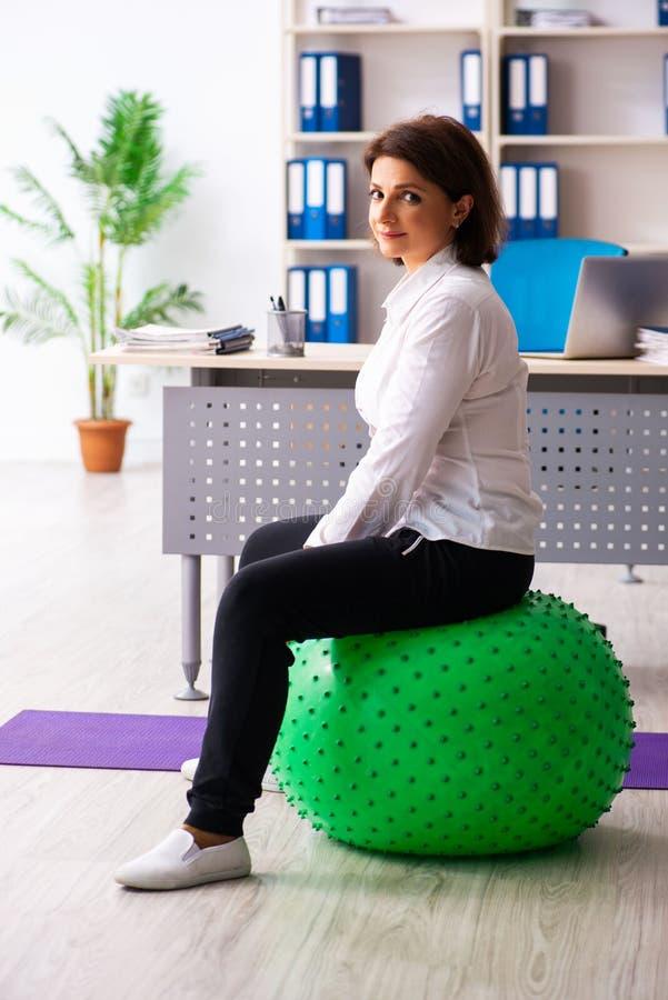 El empleado de sexo femenino de mediana edad que hace ejercicios en la oficina fotos de archivo