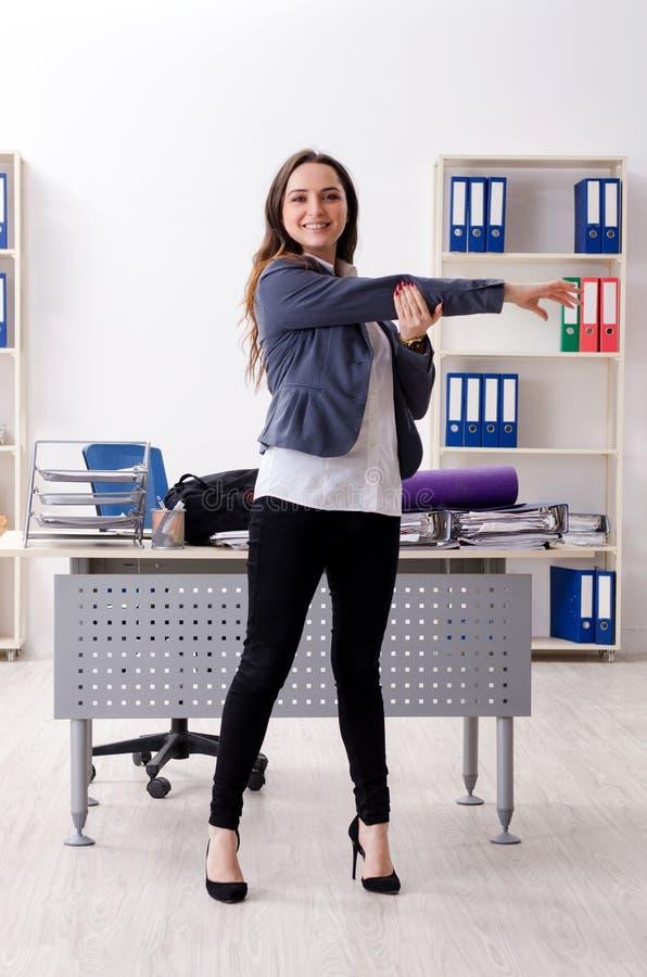 El empleado de sexo femenino que hace ejercicios del deporte en la oficina imagen de archivo