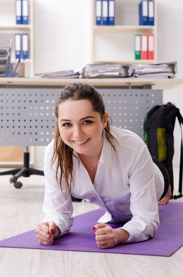 El empleado de sexo femenino que hace ejercicios del deporte en la oficina fotografía de archivo