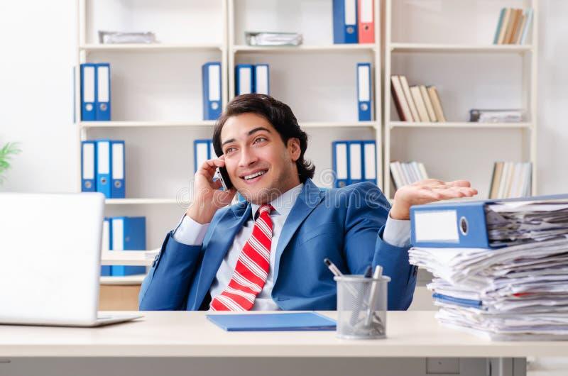 El empleado de sexo masculino feliz joven en la oficina imagenes de archivo