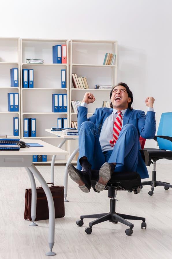 El empleado de sexo masculino feliz joven en la oficina fotos de archivo