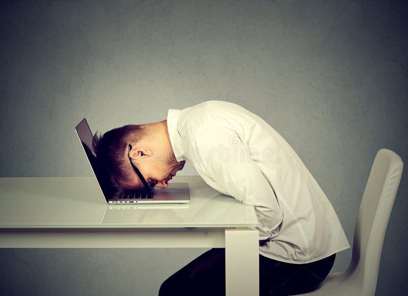 El empleado desesperado subrayó la cabeza de reclinación del hombre joven en el teclado del ordenador portátil imagen de archivo