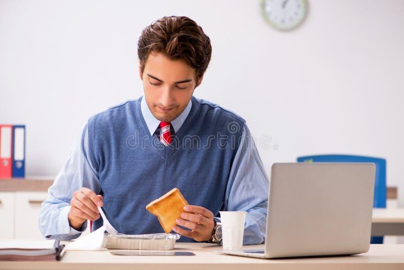 El empleado hermoso joven que trabaja en la oficina imágenes de archivo libres de regalías