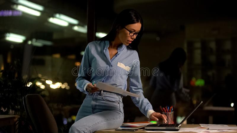 El empleado joven de la compañía con los papeles da usando el ordenador portátil, trabajando en la noche en oficina foto de archivo libre de regalías