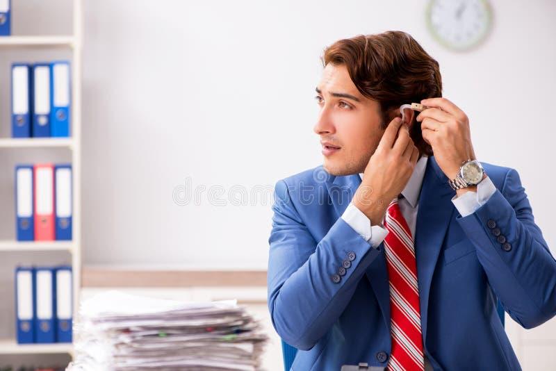 El empleado sordo que usa el audífono en oficina imágenes de archivo libres de regalías