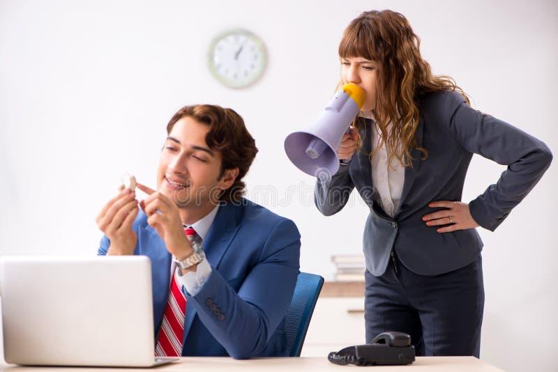 El empleado sordo que usa el audífono que habla para dirigir imagen de archivo libre de regalías