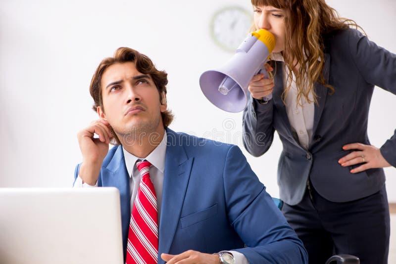 El empleado sordo que usa el aud?fono que habla para dirigir imagen de archivo libre de regalías