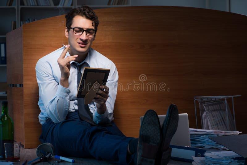 El empleado triste en la oficina que falta a su esposa después de la separación del divorcio imagen de archivo libre de regalías