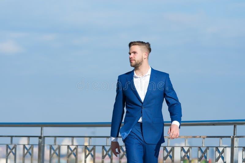 El empresario acertado del hombre de negocios en traje camina día soleado al aire libre, fondo del cielo Hombre confiado y prepar imagenes de archivo
