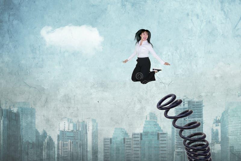El empresario de sexo femenino salta usando una primavera grande imágenes de archivo libres de regalías