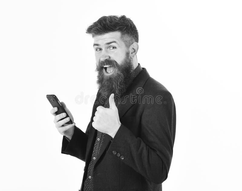 El empresario sonriente del hombre está leyendo buenas noticias vía móvil fotografía de archivo libre de regalías
