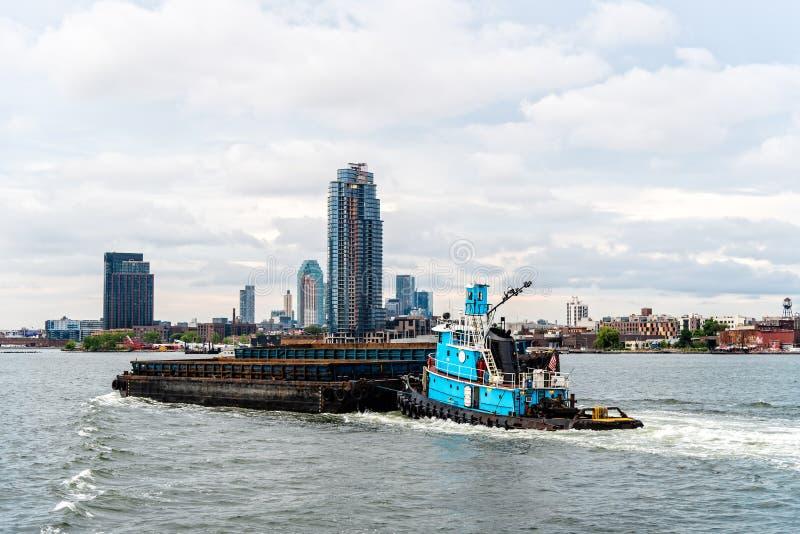 El empujar del remolcador barge adentro New York City foto de archivo libre de regalías