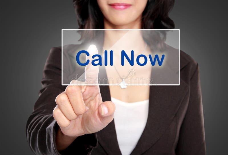 El empuje de la mujer de negocios ahora a llamar abotona en la pantalla virtual foto de archivo