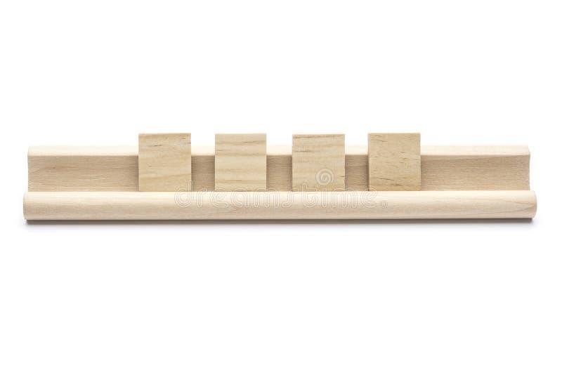 El en blanco cuatro se arrastra las tejas en un estante de madera fotografía de archivo