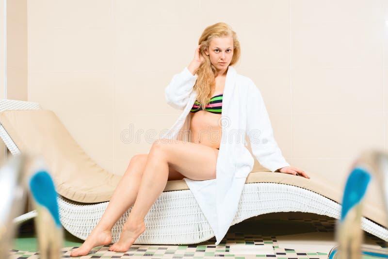 El encantar rubio en un bañador chica joven que miente en el sofá en el salón del balneario mujer en una albornoz blanca fotografía de archivo libre de regalías