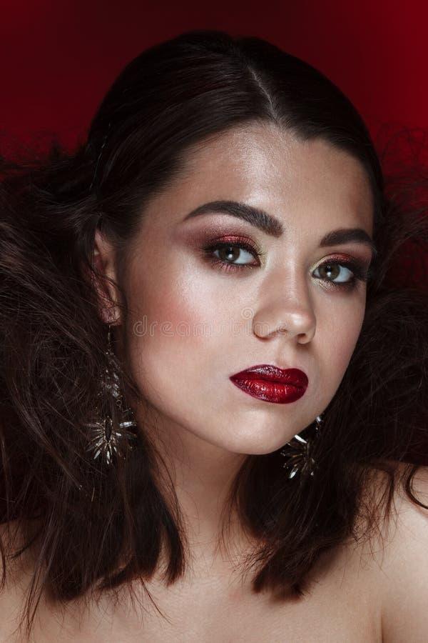 El encanto femenino del retrato de la belleza compone en fondo rojo imágenes de archivo libres de regalías