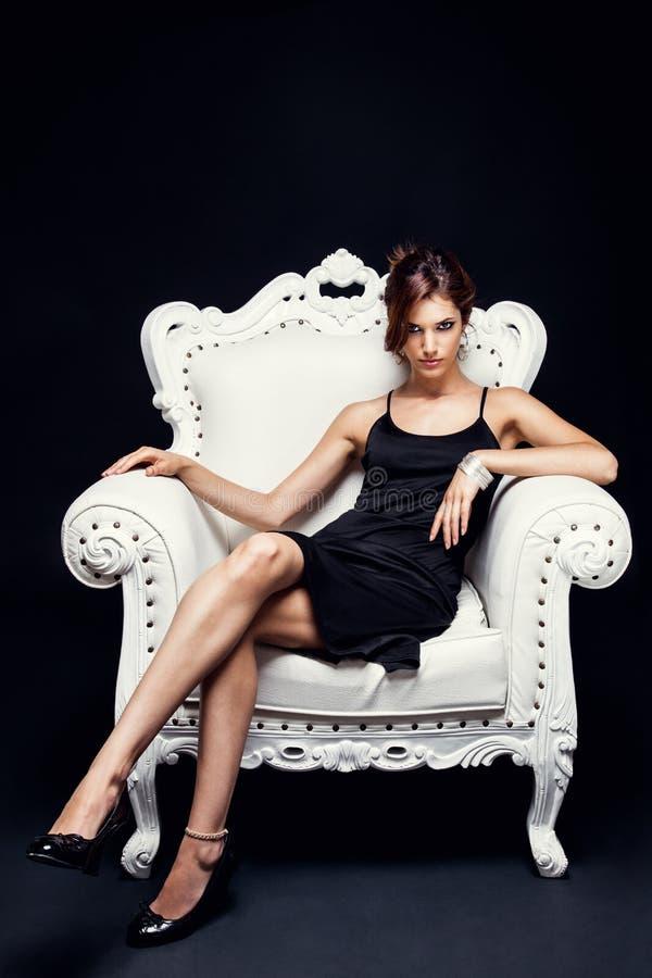 Mujer joven hermosa en una silla imagenes de archivo