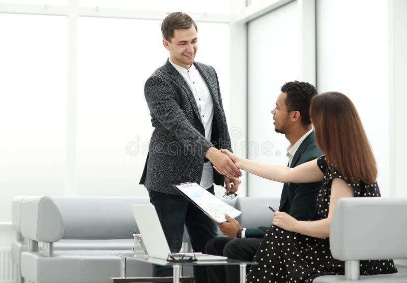 El encargado acoge con satisfacción a clientes en el pasillo del banco imagen de archivo libre de regalías