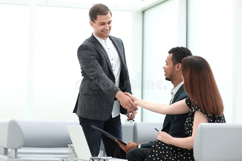 El encargado acoge con satisfacción a clientes en el pasillo del banco foto de archivo
