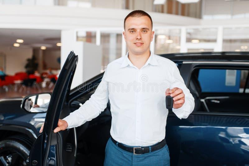 El encargado da dominante al nuevo coche en la sala de exposición imagenes de archivo