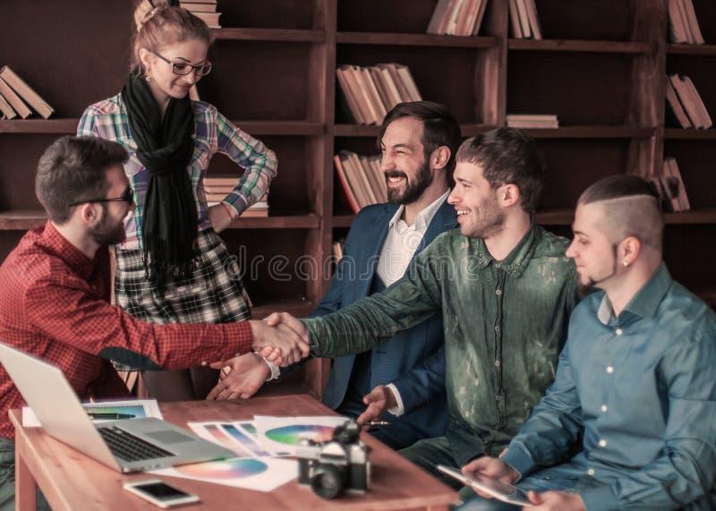 El encargado de publicidad con un apret?n de manos saluda al cliente fotografía de archivo