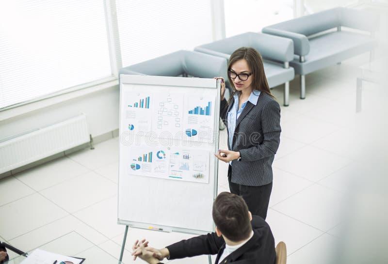 El encargado de sexo femenino conduce la presentación del márketing en una oficina moderna fotos de archivo