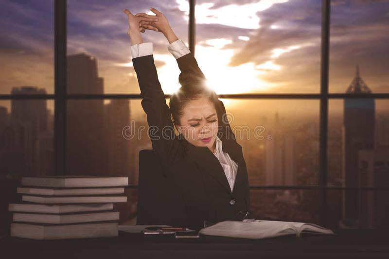 El encargado de sexo femenino estira los brazos después de trabajado demasiado imagen de archivo