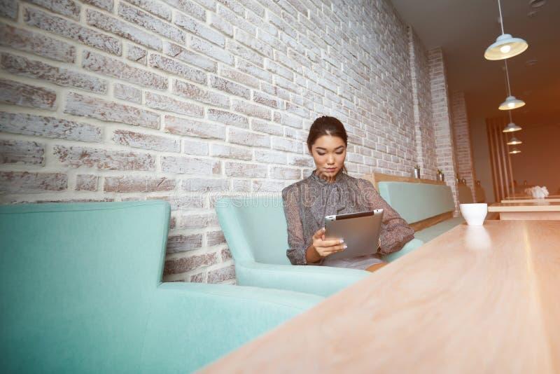 El encargado de sexo femenino magnífico joven de la cafetería moderna está haciendo el nuevo menú en la tableta digital portátil, imagenes de archivo