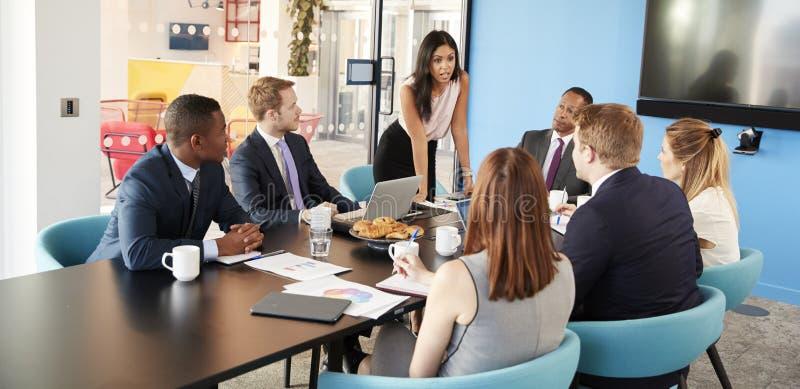 El encargado de sexo femenino se coloca que se dirige a colegas en sala de reunión imagen de archivo libre de regalías