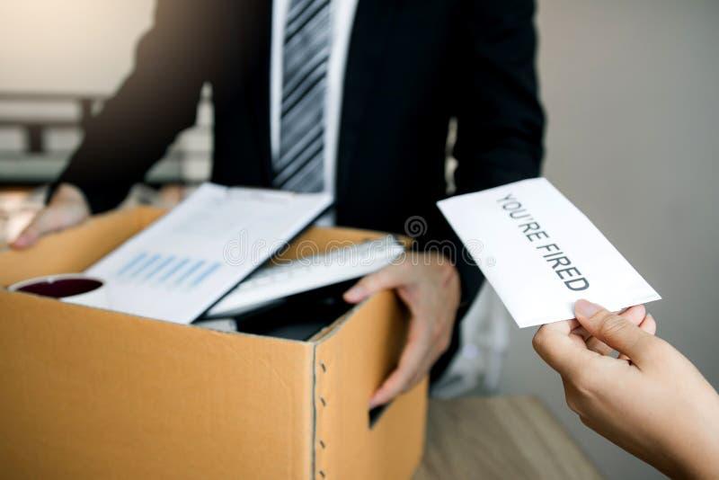 El encargado de sexo femenino somete una carta de dimisión o un sobre al empleado de sexo masculino en la oficina fotos de archivo