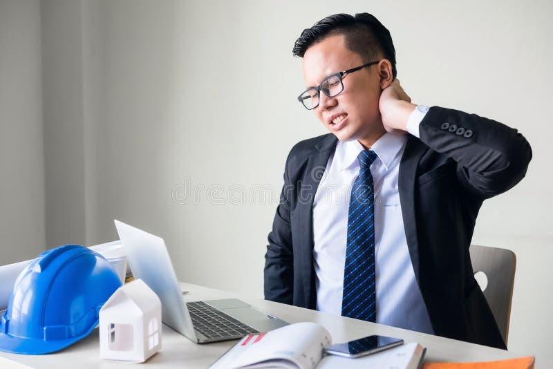 el encargado del ingeniero de negocio sufre el dolor del cuello fotografía de archivo libre de regalías