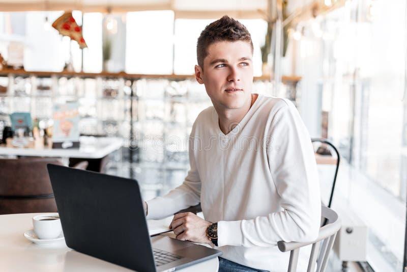 El encargado joven atractivo se está sentando en un café y está trabajando en un ordenador portátil en un proyecto del negocio Tr fotos de archivo libres de regalías