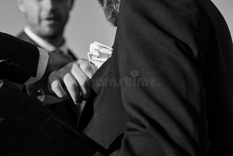El encargado pone el dinero en el bolsillo en fondo del cielo azul imagen de archivo libre de regalías