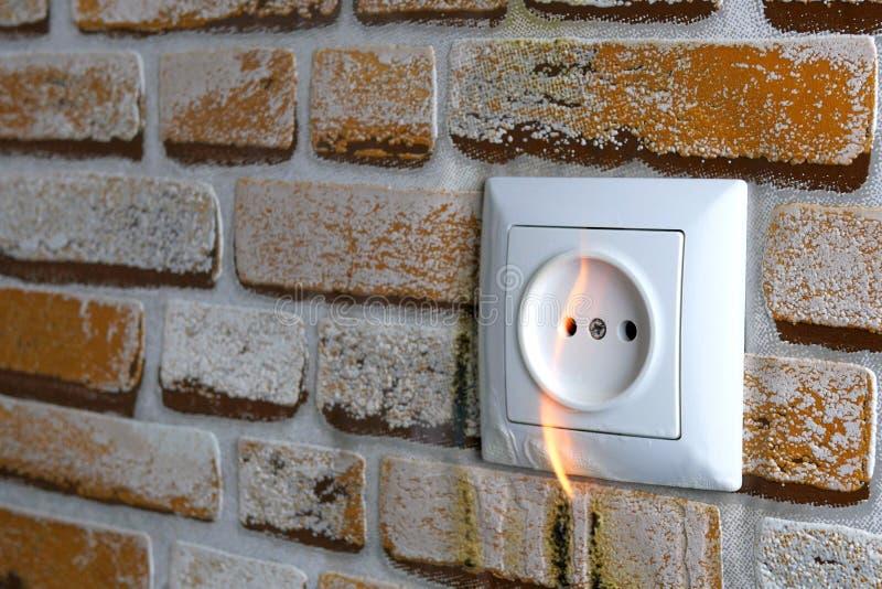 El enchufe eléctrico se quema en la pared de la casa. Cortocircuito y peligro de incendio. Tal vez la red eléctrica esté sobrec foto de archivo