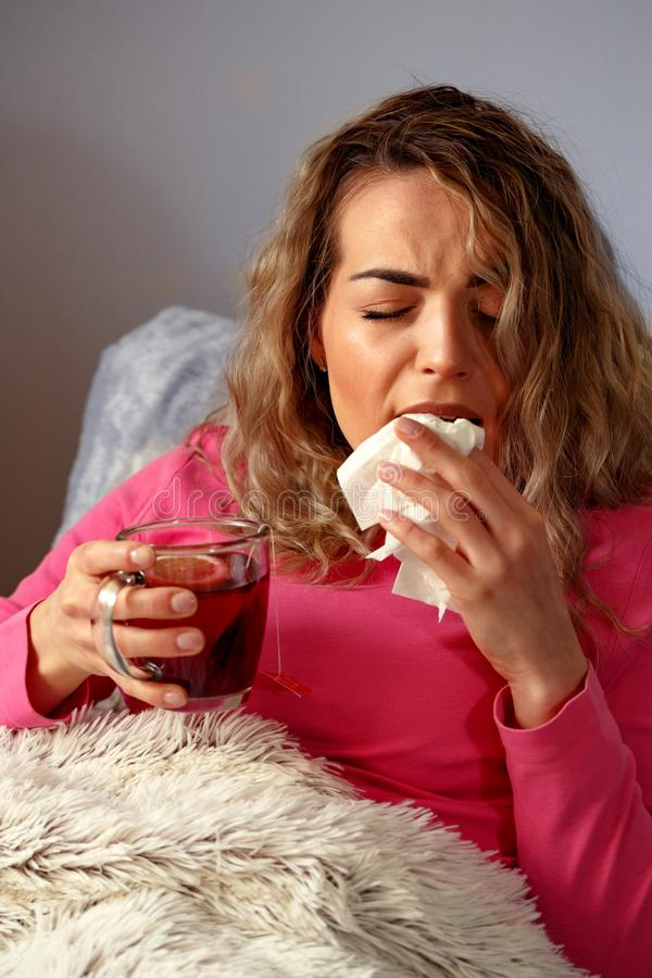 El enfermo de la mujer en cama con temperatura bebe té caliente en casa imágenes de archivo libres de regalías