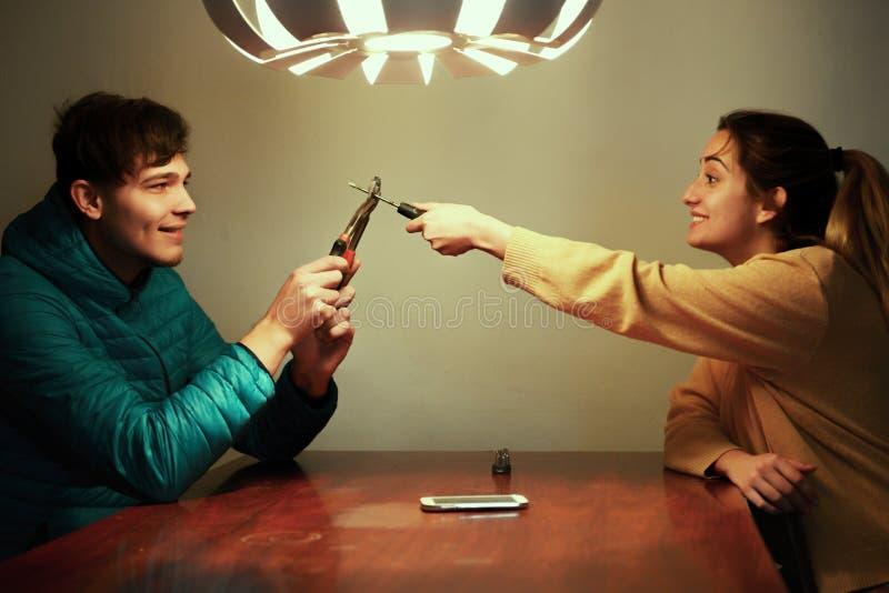 El engañar, hombre y mujer de los amigos jugando con los alicates y destornillador imagen de archivo