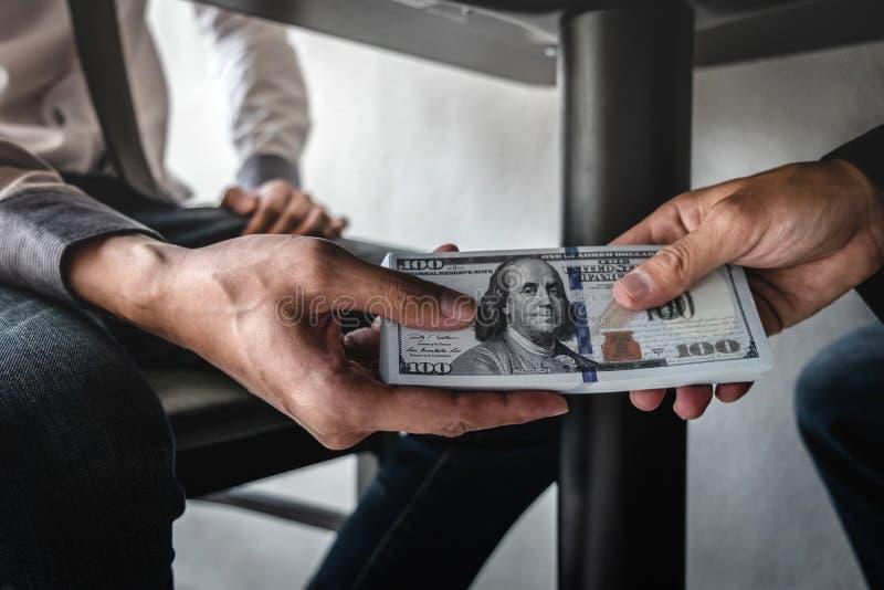 El engaño deshonesto en el dinero ilegal del negocio, hombre de negocios recibe el dinero del soborno debajo de la tabla a los ho fotografía de archivo