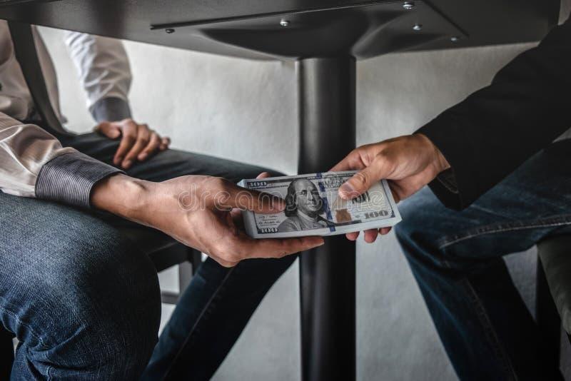 El enga?o deshonesto en el dinero ilegal del negocio, hombre de negocios recibe el dinero del soborno debajo de la tabla a los ho foto de archivo