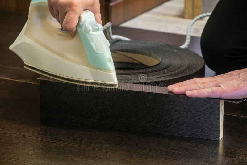 El ensamblador del fabricante de los muebles pega el borde de la melamina a la hoja laminada del conglomerado imágenes de archivo libres de regalías