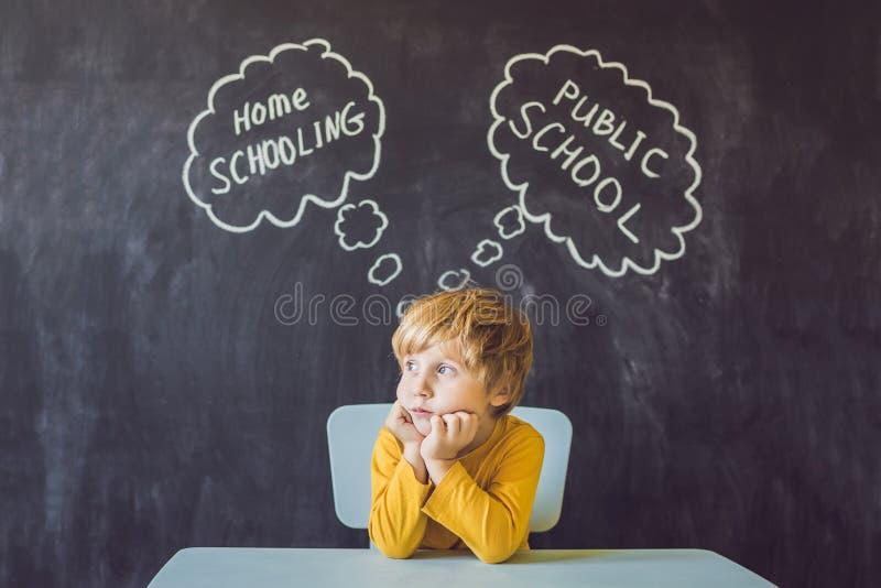 El enseñar en casa contra escuelas públicas - el muchacho se sienta en la tabla y elige entre enseñar casero y escuela pública -  imagen de archivo libre de regalías