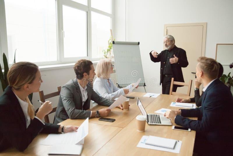 El entrenador mayor que da la presentación a los encargados ejecutivos combina en b foto de archivo libre de regalías