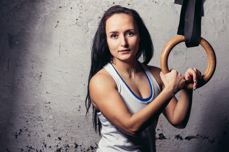 El entrenamiento de la mujer de la aptitud arma con los anillos de la gimnasia en el gimnasio imagen de archivo libre de regalías