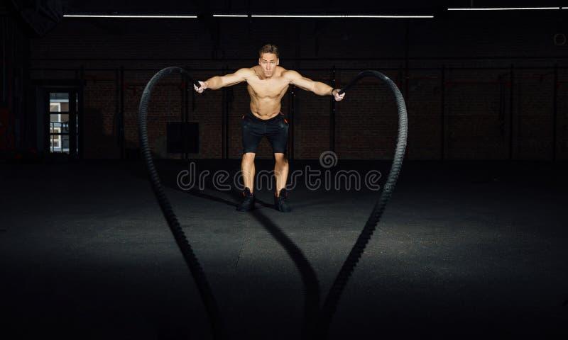 El entrenamiento del hombre de la aptitud con batalla ropes en el gimnasio cuerpo cabido ejercicio de formación en club torso fotografía de archivo libre de regalías