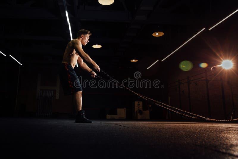 El entrenamiento del hombre de la aptitud con batalla ropes en el gimnasio cuerpo cabido ejercicio de formación en club torso foto de archivo