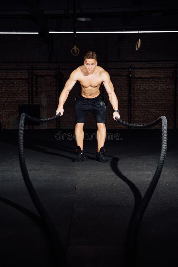 El entrenamiento del hombre de la aptitud con batalla ropes en el gimnasio cuerpo cabido ejercicio de formación en club torso imágenes de archivo libres de regalías