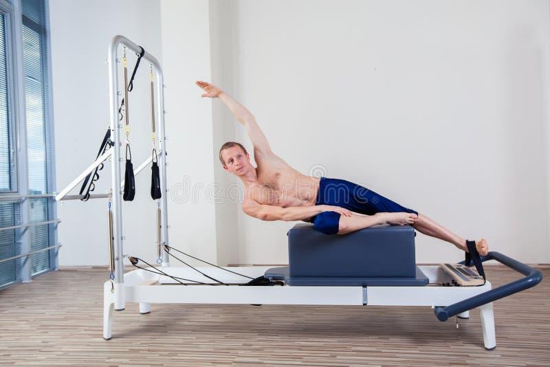 El entrenamiento del reformador de Pilates ejercita al hombre en el gimnasio imagen de archivo libre de regalías