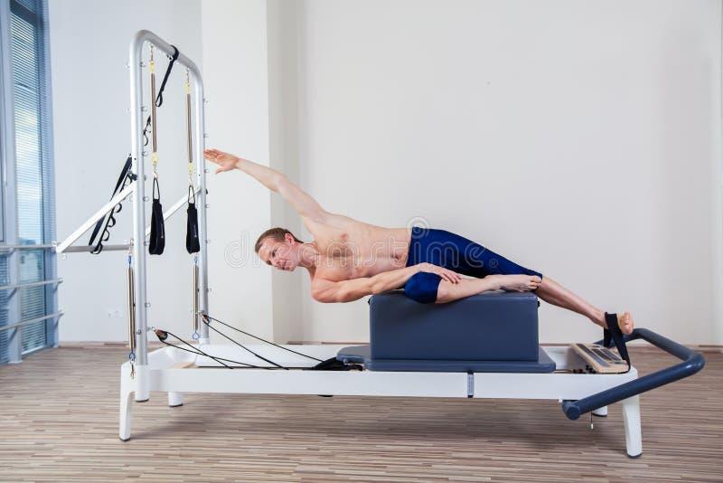 El entrenamiento del reformador de Pilates ejercita al hombre en el gimnasio foto de archivo