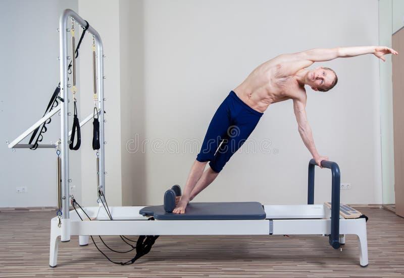 El entrenamiento del reformador de Pilates ejercita al hombre en el gimnasio foto de archivo libre de regalías